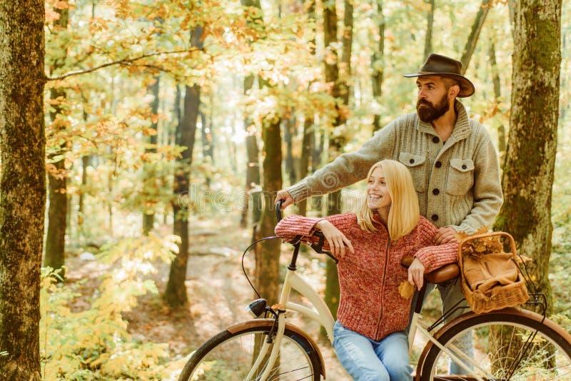 Ideas para la fecha perfecta del otoño Fecha romántica con la bicicleta Hombre barbudo y mujer que se relajan en el bosque del ot fotos de archivo