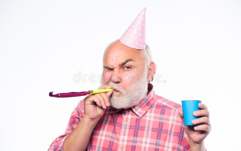 Ideas for seniors birthday celebrations. Man bearded grandpa with birthday cap and drink cup. Grandfather graybeard. Blowing party whistle. Getting older is stock image