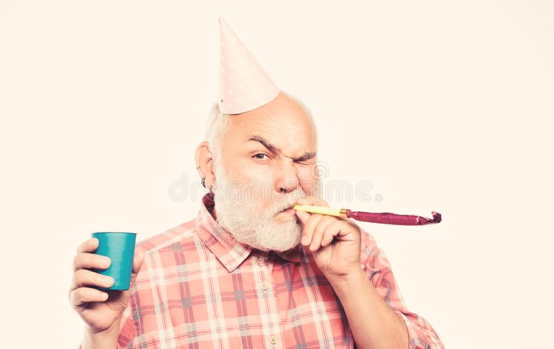 Ideas for seniors birthday celebrations. Man bearded grandpa with birthday cap and drink cup. Grandfather graybeard stock image