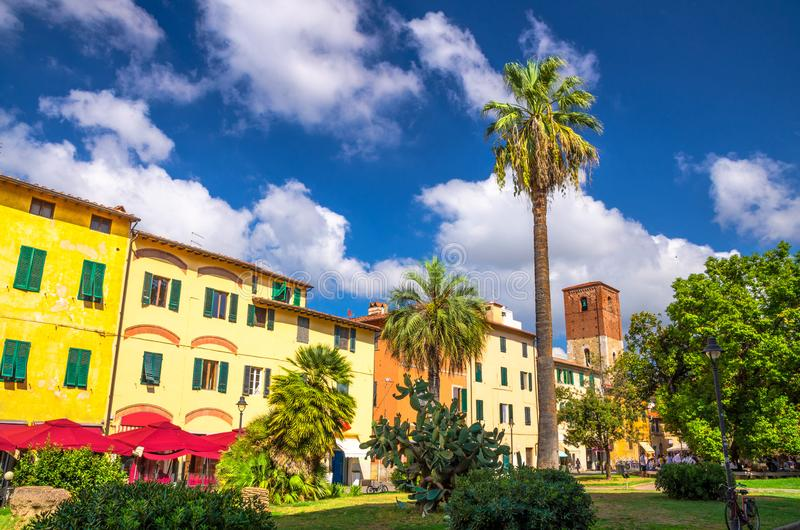 Idee In Circolo park with palms, colorful buildings and bell tower on Piazza Dante Alighieri square in historical centre of Pisa stock photo