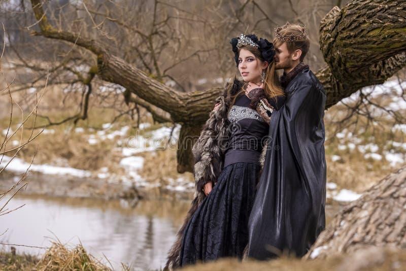 Idee di cosplay I giovani accoppiano la posa come principe e principessa sulla chiusura antica nella foresta di primavera fotografia stock libera da diritti