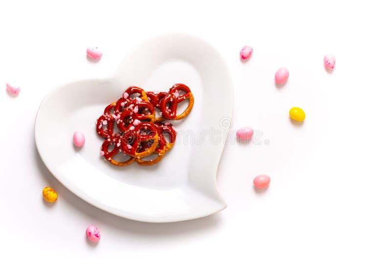 Idee für Valentinsgruß behandelt Brezelbadschokolade in der keramischen Herzformplatte auf weißem Hintergrund mit Kopienraum lizenzfreie stockfotos