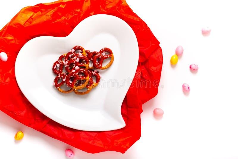 Idee für Valentinsgruß behandelt Brezelbadschokolade in der keramischen Herzformplatte auf weißem Hintergrund mit Kopienraum lizenzfreie stockbilder