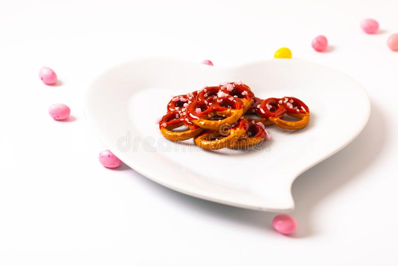 Idee für Valentinsgruß behandelt Brezelbadschokolade in der keramischen Herzformplatte auf weißem Hintergrund mit Kopienraum stockfotos