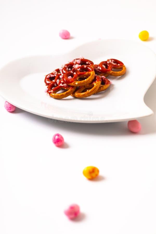 Idee für Valentinsgruß behandelt Brezelbadschokolade in der keramischen Herzformplatte auf weißem Hintergrund mit Kopienraum lizenzfreies stockbild