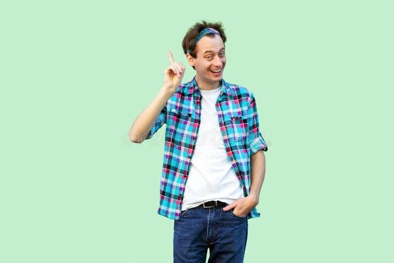 Idee Portret van de opgewekte genie jonge mens in toevallig blauw geruit overhemd en hoofdband die en zich camera met gelukkig be royalty-vrije stock afbeelding