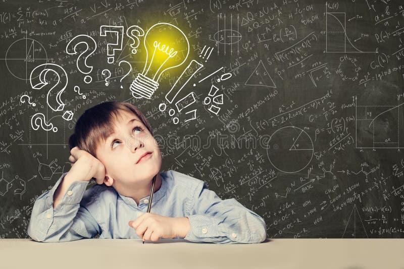 Idee! Slimme jong geitjestudent met lightbulb op bord stock fotografie
