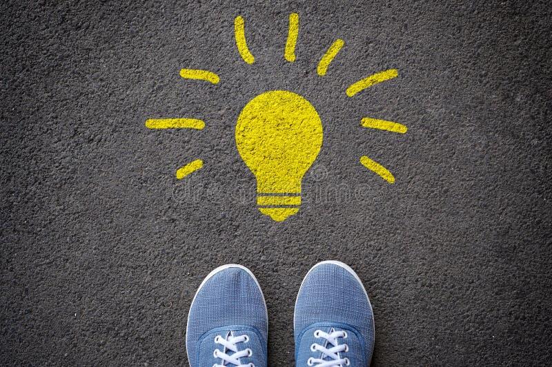 Ideeneinblickkonzept Füße in den Blue Jeans-Turnschuhen, die nahe einer hellen Lampe auf dem Asphalt stehen lizenzfreies stockfoto