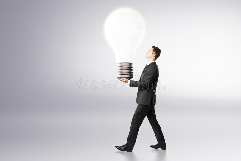Ideenkonzept mit Geschäftsmann trägt große Glühlampe stockfotografie