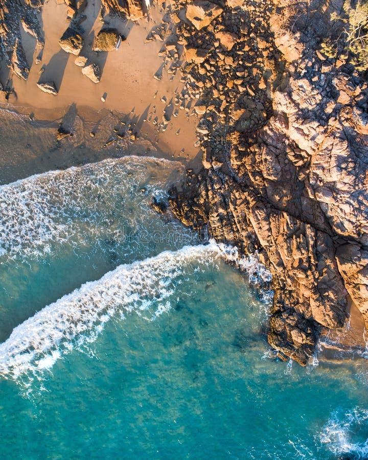 Ideia aérea bonita de um escape da praia com praia agradável, rochas e as ondas delicadas mornas fotos de stock royalty free