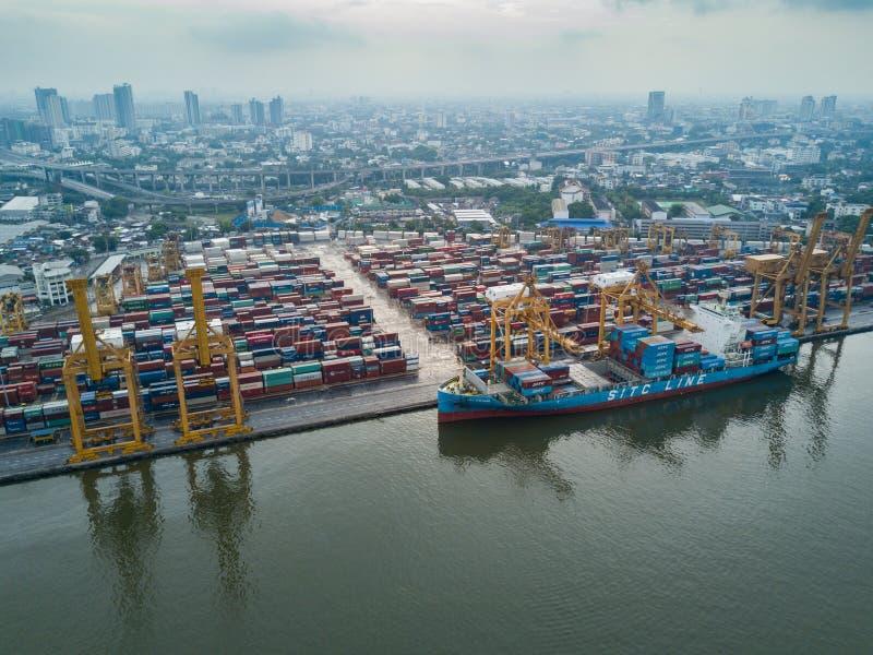 Ideia aérea da logística e transporte do navio e do Crane Bridge de carga do recipiente com fundo de construção da arquitetura da fotografia de stock