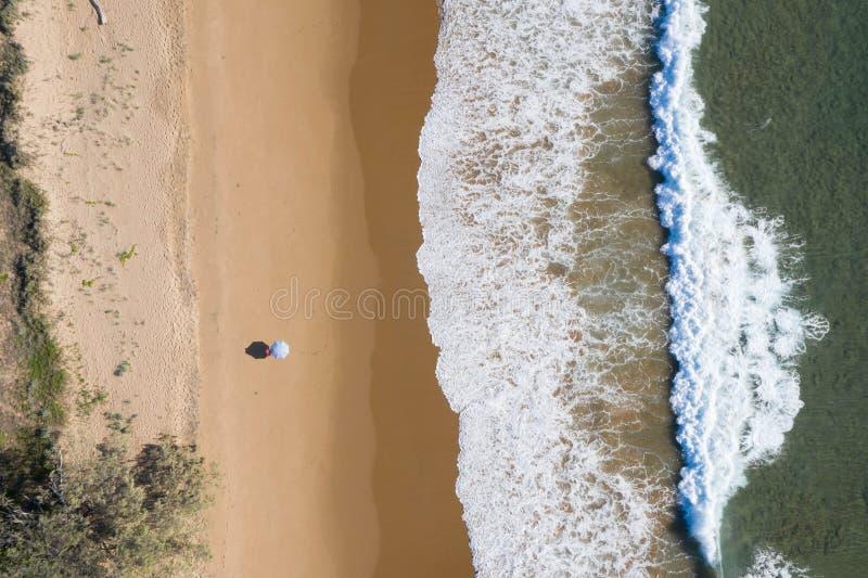 Ideia aérea da praia dos guarda-chuvas, das ondas, do oceano dos azuis e de vibrações de relaxamento fotos de stock royalty free