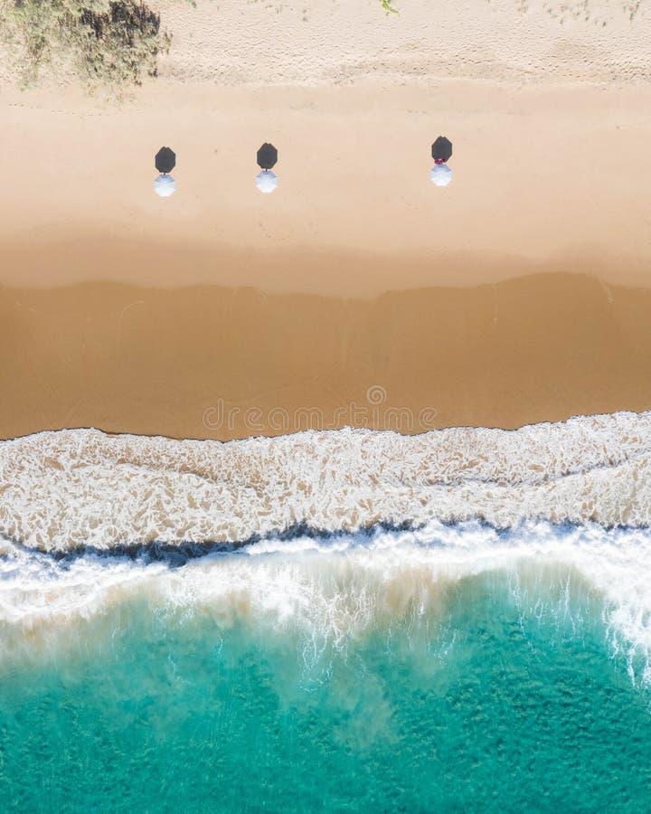 Ideia aérea da praia dos guarda-chuvas, das ondas, do oceano dos azuis e de vibrações de relaxamento imagens de stock