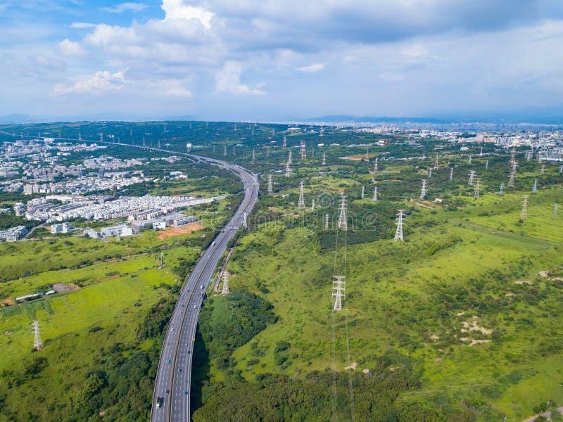 Ideia aérea das estradas e do cargo de alta tensão do metal na propriedade industrial Torre da eletricidade Vista superior de árv fotografia de stock