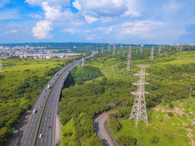 Ideia aérea das estradas e do cargo de alta tensão do metal na propriedade industrial Torre da eletricidade Vista superior de árv fotografia de stock royalty free