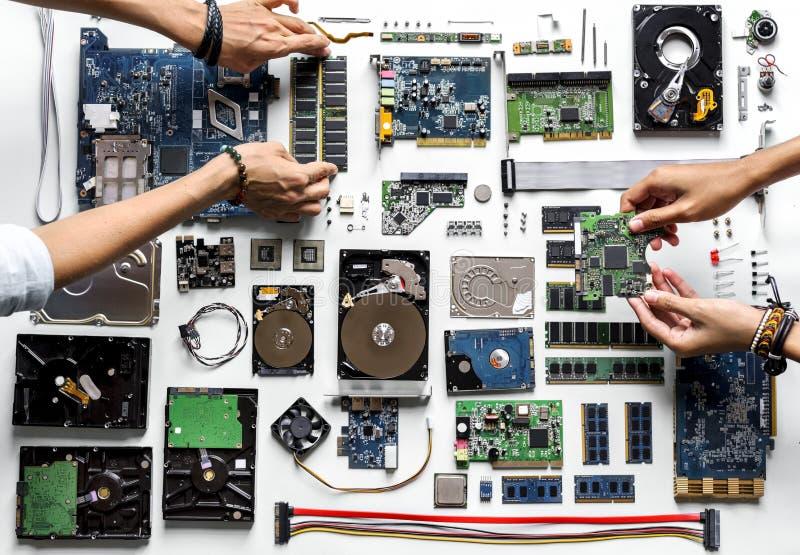 A ideia aérea das mãos com eletrônica do computador parte no fundo branco