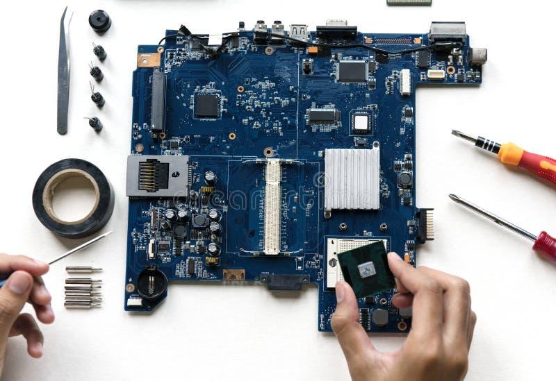 A ideia aérea das mãos com eletrônica do computador parte no fundo branco imagens de stock