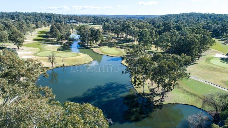A ideia aérea de fairways e de verde do campo de golfe com a bandeira, os depósitos e a represa molha o perigo cercados por árvor fotografia de stock