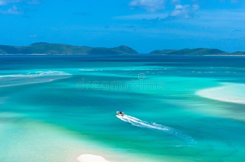Ideia aérea de transportar o barco que move-se na água azul de turquesa fotografia de stock