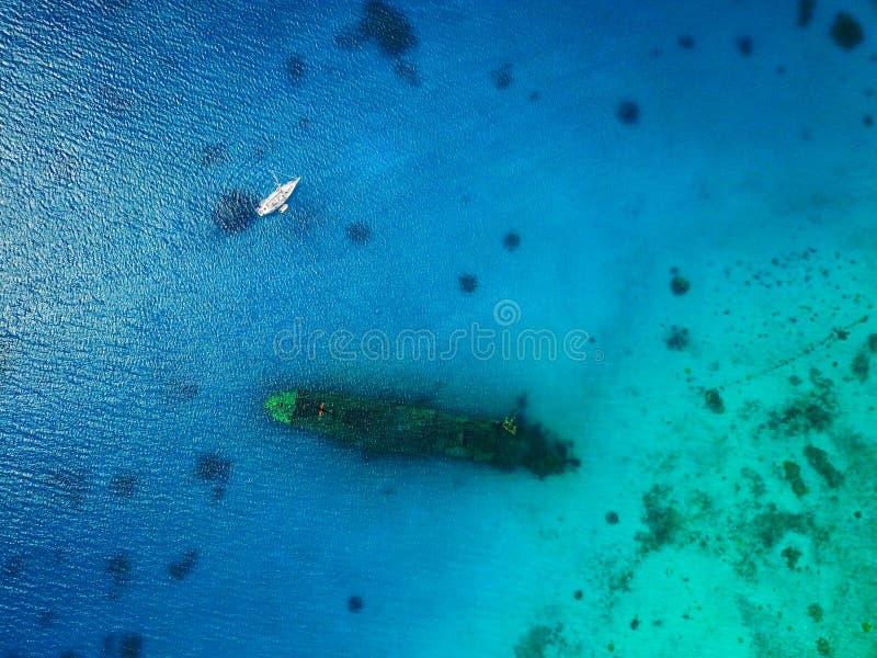 Ideia aérea de uma destruição afundado do navio de WWII com um iate ancorado, água clara vibrante fotografia de stock