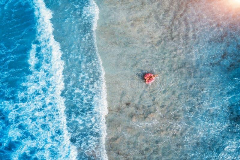 Ideia aérea de uma natação da jovem mulher com o anel da nadada da filhós fotos de stock royalty free