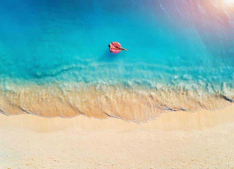 Ideia aérea de uma natação da jovem mulher com o anel da nadada da filhós fotografia de stock