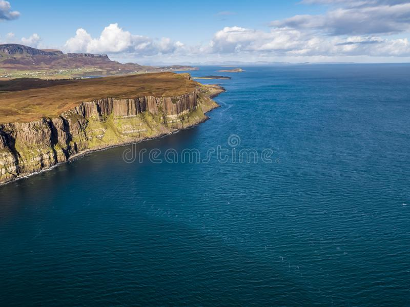 Ideia aérea do litoral dramático nos penhascos por Staffin com a cachoeira famosa da rocha do kilt - ilha de Skye - fotografia de stock
