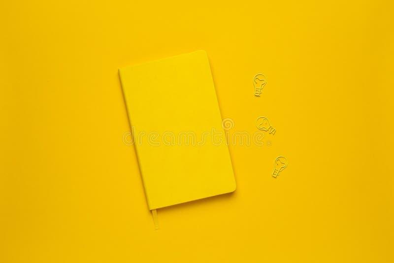 Ideia amarela da ampola do caderno e do clipe no fundo amarelo imagens de stock royalty free