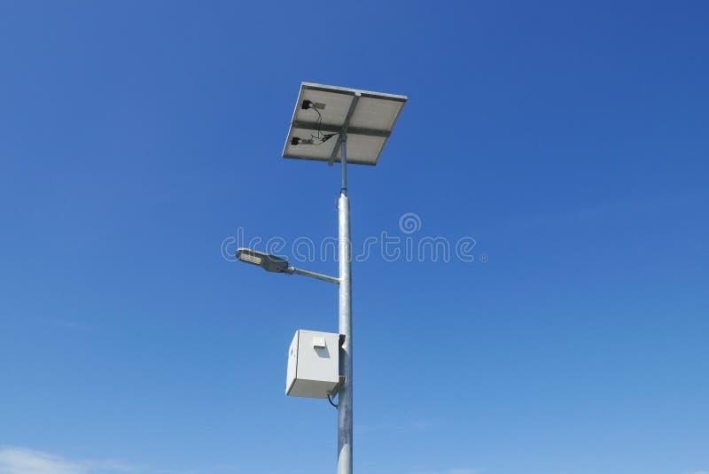 Ideia ascendente próxima da luz de rua do diodo emissor de luz com célula solar no fundo claro do céu azul com nuvens foto de stock