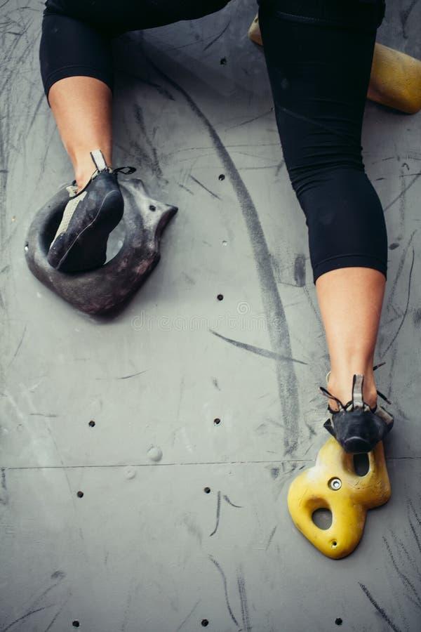 Ideia ascendente próxima da parte inferior dos pés fêmeas do montanhista de rocha na parede de escalada artificial fotos de stock royalty free