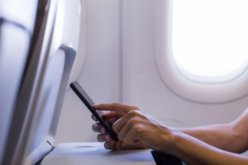 Ideia ascendente próxima das mãos fêmeas usando um telefone celular em um plano conceito do curso foto de stock