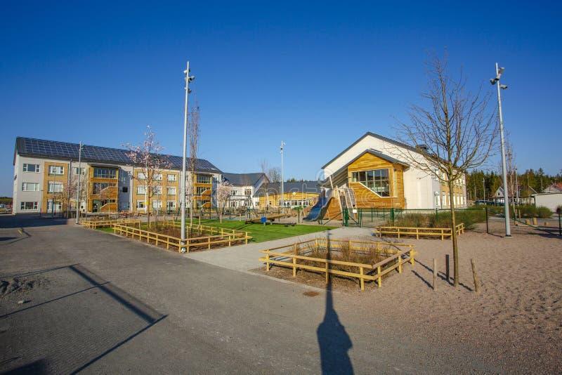 Ideia bonita de deixar a área Casa com painéis solares e prédio da escola com lugar das crianças da atividade exterior imagens de stock