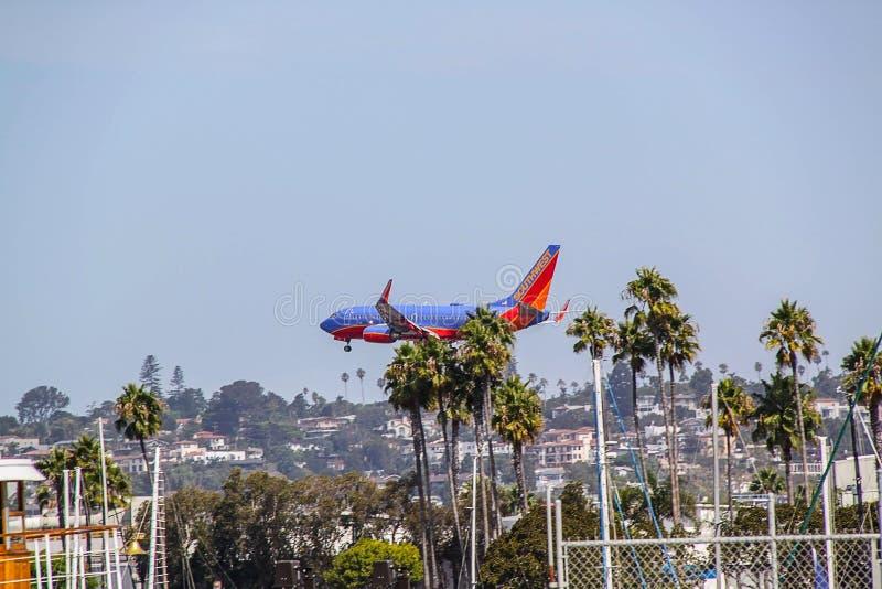 Ideia bonita do momento enorme da aterrissagem de avião Céu azul e palmeiras verdes San Diego EUA foto de stock royalty free