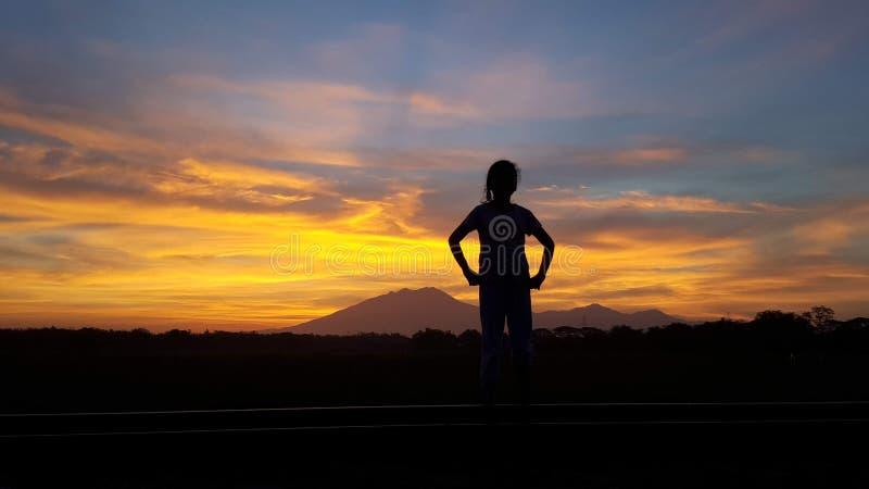 Ideia bonita do nascer do sol do silluete da menina foto de stock