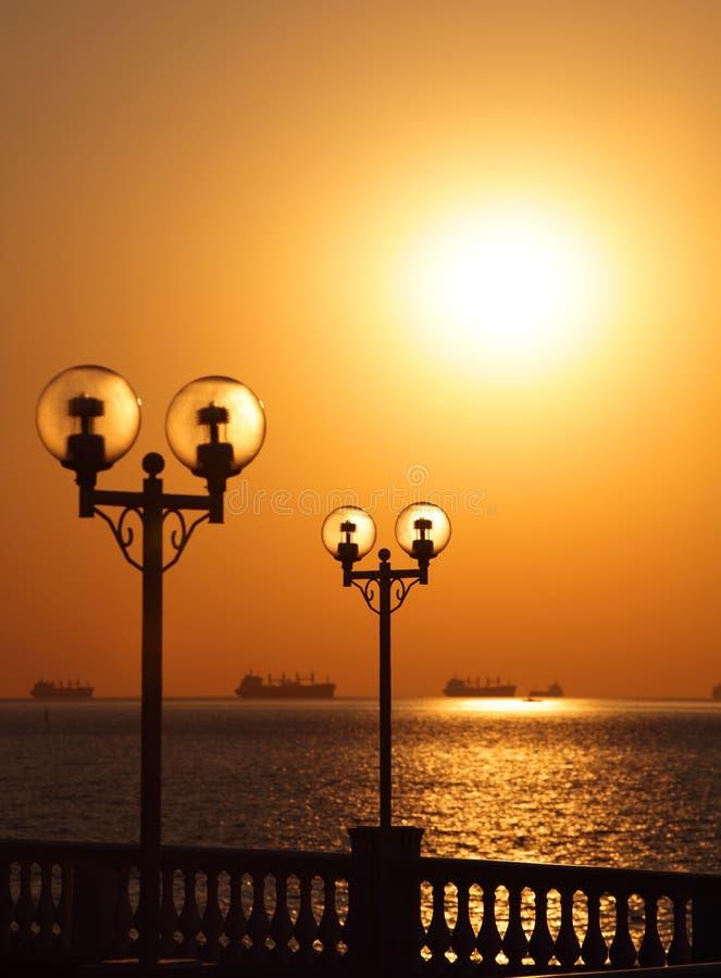Ideia cênico da margem com as lanternas retroiluminadas pelo sol de ajuste e com os navios no roadstead fotos de stock royalty free