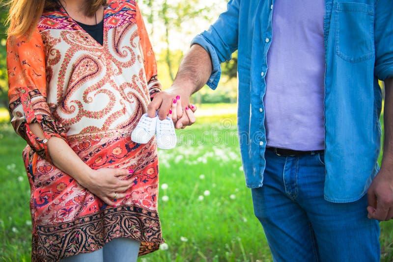 A ideia colhida do tiro da espera parents guardar sapatas de bebê Conceito da gravidez, o de maternidade e o novo de família foto de stock