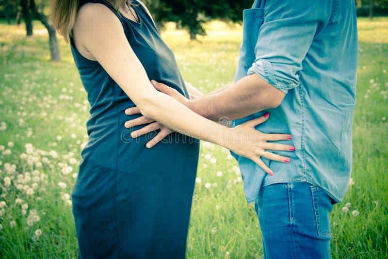 A ideia colhida do tiro da espera parents o aperto e guardar da barriga Conceito da gravidez, o de maternidade e o novo de famíli imagens de stock royalty free