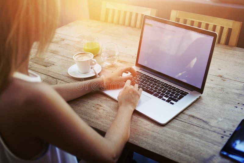 Ideia colhida do tiro da introdução da jovem mulher no laptop com a tela vazia do espaço da cópia ao sentar-se no café fotografia de stock royalty free