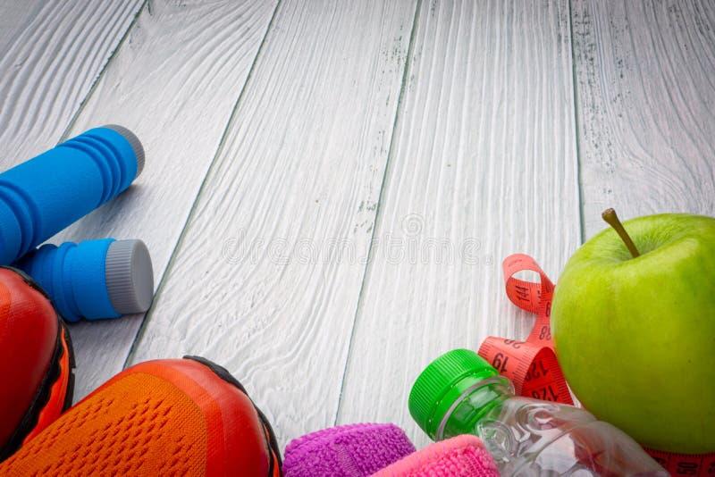 Ideia colocada superior ou lisa da toalha, da água, do fruto da maçã, das sapatas do esporte e da corda de salto com área de espa foto de stock