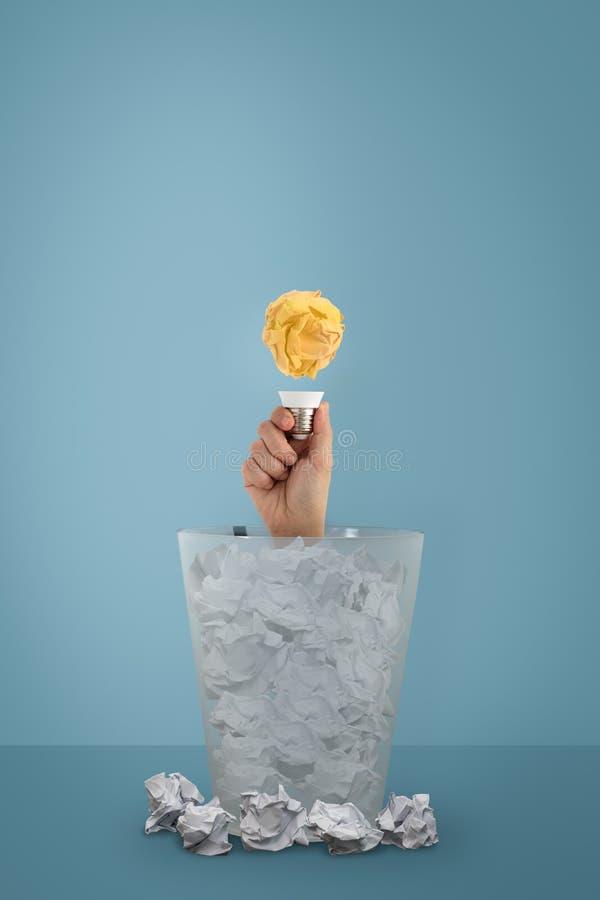 A ideia com bola e a ampola de papel, a mão da mulher apareceu do lixo fotografia de stock royalty free