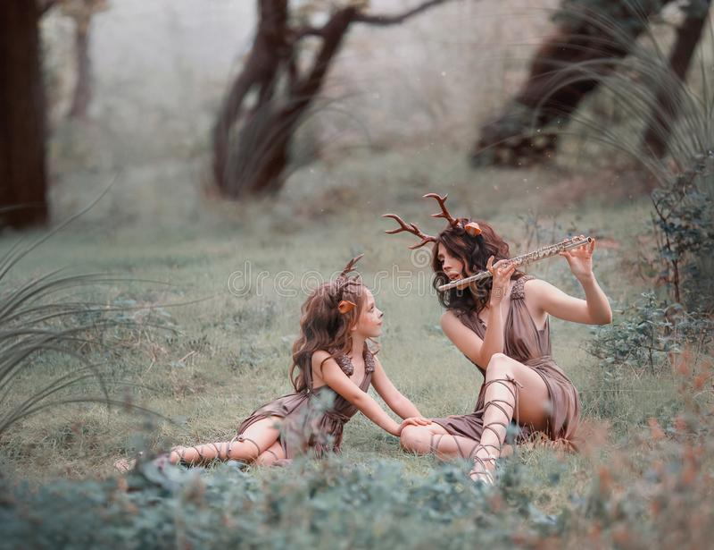 A ideia criativa da foto para a mamã e a filha, a criança e a mãe vestidas como cervos estão sentando-se na grama na floresta, a foto de stock