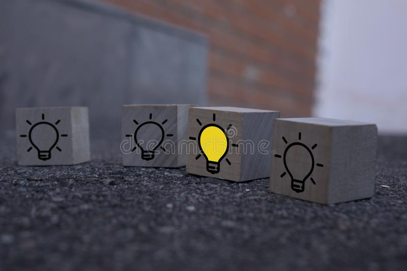 Ideia criativa, nova ideia, inovação e conceito de solução cubos de madeira com o símbolo da lâmpada amarela sobre a mesa, fundo  fotos de stock royalty free