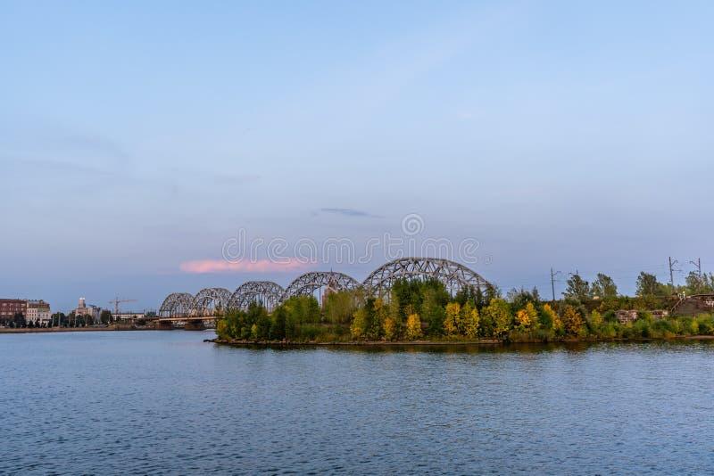 Ideia da arquitetura da cidade com a ponte de estrada de ferro em Riga, Letónia, na hora azul, crepuscular com um espaço livre pa imagem de stock royalty free