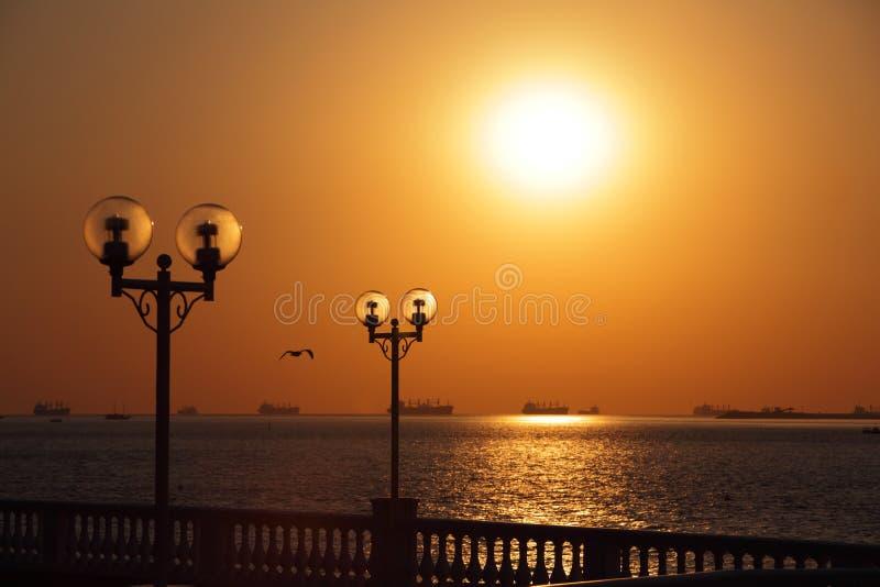 Ideia da margem com as lanternas retroiluminadas pelo sol de ajuste e com os navios no roadstead imagem de stock