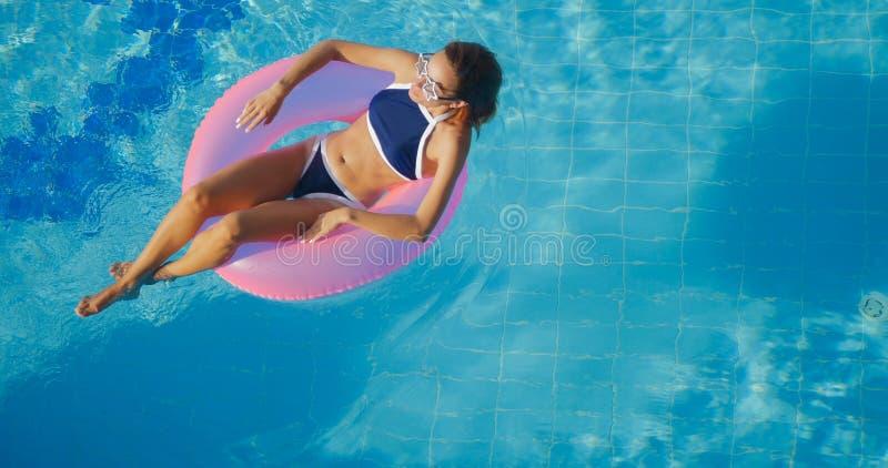 Ideia da natação moreno nova da mulher no anel cor-de-rosa inflável imagens de stock royalty free