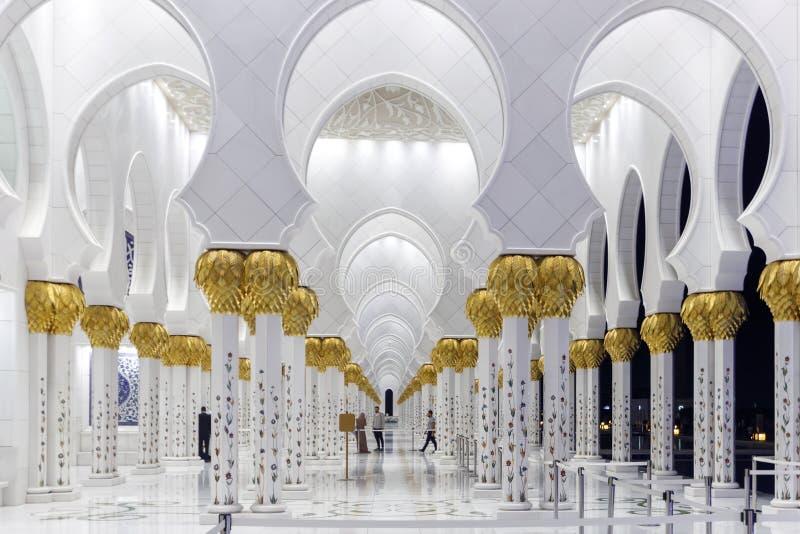 Ideia da passagem através dos arcos de Sheikh Zayed Grand Mosque com as colunas de mármore ornamentados com imagens do ouro e dos foto de stock