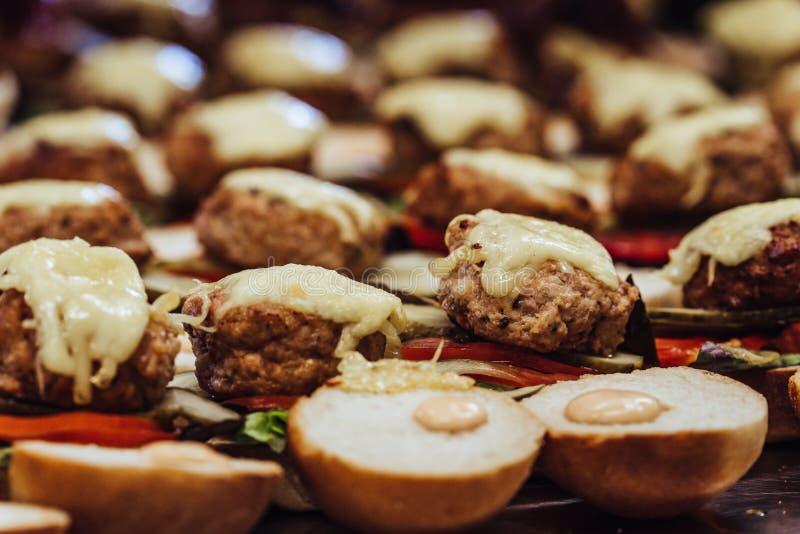 Ideia da propagação cortada do pão na tabela com os ingredientes neles para hamburgueres pequenos - grupo do close up da cozinha, foto de stock royalty free
