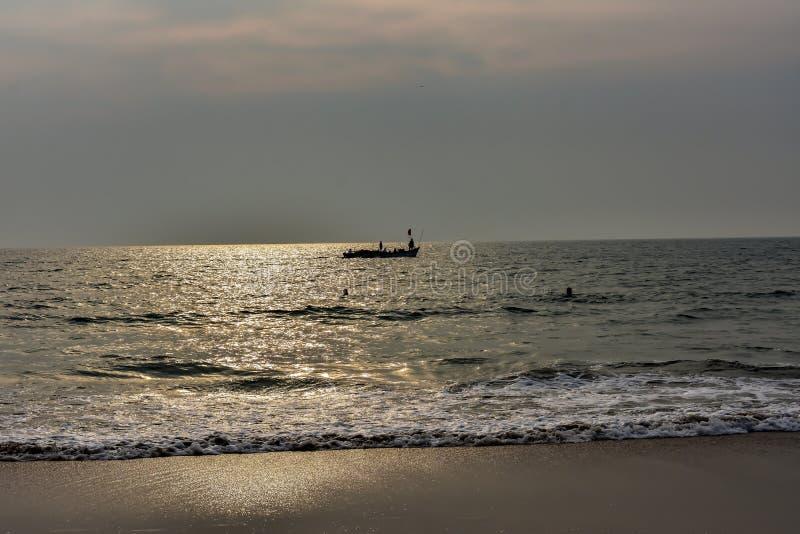 A ideia da refração da luz do sol dourada na praia do mar com a silhueta de um barco criou um fundo mágico fotos de stock royalty free