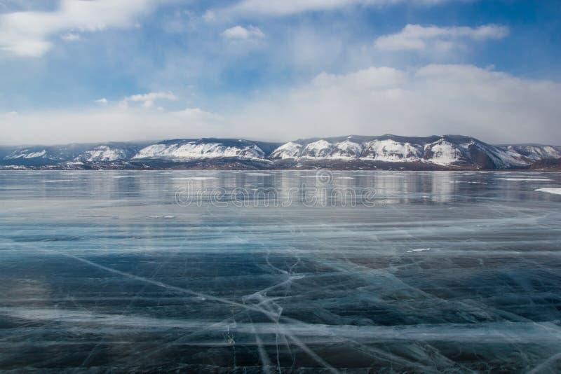 ideia da superfície da água de gelo sob o céu nebuloso durante o dia com os montes na costa, Rússia, lago imagem de stock royalty free