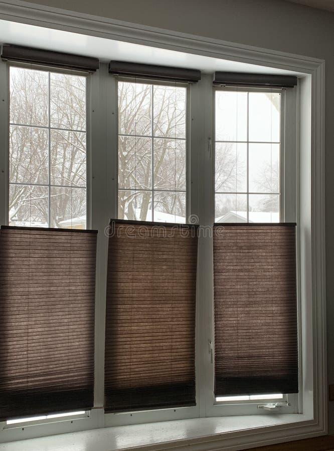 Ideia da tempestade de neve através da janela de baía com a metade das cortinas abaixada durante o inverno foto de stock royalty free